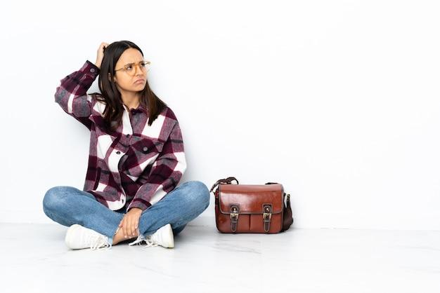 Donna giovane studente seduto sul pavimento con dubbi mentre grattando la testa Foto Premium