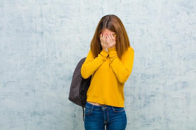 Donna giovane studente sentirsi triste, frustrato, nervoso e depresso, coprendosi il viso con entrambe le mani, piangendo contro la parete del grunge Foto Premium
