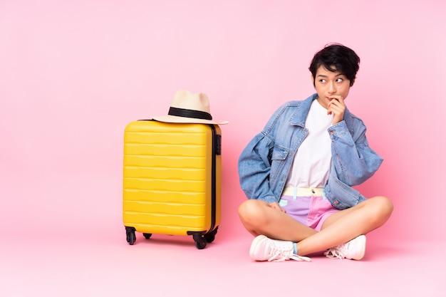 Donna giovane viaggiatore con la valigia che si siede sul pavimento sopra il muro rosa con dubbi e con espressione del viso confuso Foto Premium