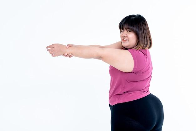 Donna grassa asiatica che allunga le braccia per rilassare i muscoli Foto Premium
