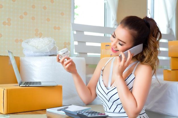 Donna graziosa che guarda un prodotto durante lo smartphone di colloquio Foto Premium