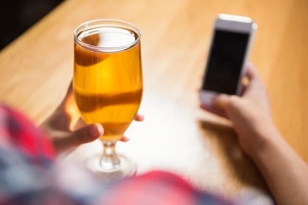 Donna graziosa che per mezzo dello smartphone e mangiando una birra Foto Premium