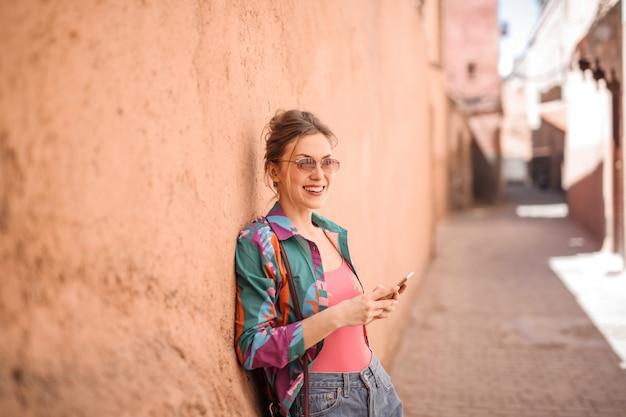 Donna graziosa che per mezzo dello smartphone sulla via di marrakesh Foto Premium