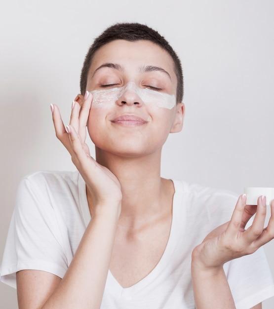 Donna graziosa che usando una crema per la pelle Foto Gratuite