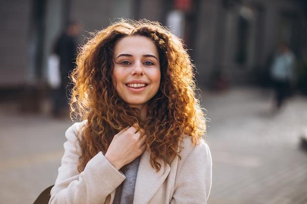 Donna graziosa con capelli ricci che cammina in un cappotto di autunno Foto Gratuite