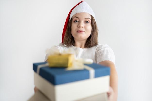 Donna graziosa contenta in cappello di santa che dà mucchio dei regali di natale Foto Gratuite