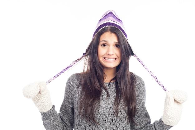 Donna graziosa del brunette con un cappello peruviano di lana un maglione e guanti che ha freddo Foto Premium