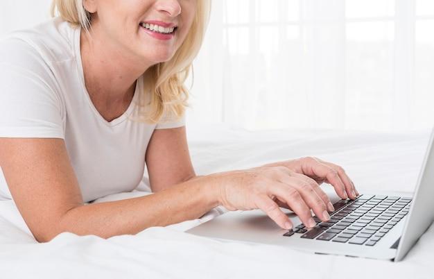 Donna graziosa del primo piano con sorridere del computer portatile Foto Gratuite