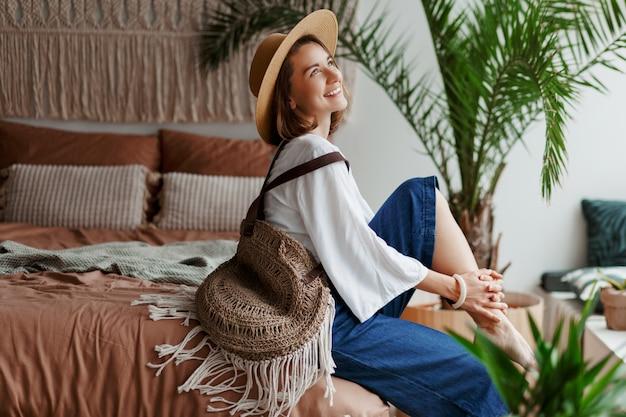 Donna graziosa elegante in cappello di paglia e camicetta bianca in posa a casa, seduto sul letto Foto Gratuite