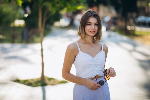Donna graziosa in attrezzatura di estate in parco Foto Gratuite