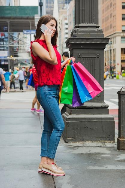 Donna graziosa in jeans che telefona con i sacchetti della spesa Foto Gratuite