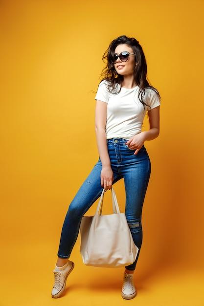 Donna graziosa in occhiali da sole con borsa Foto Premium