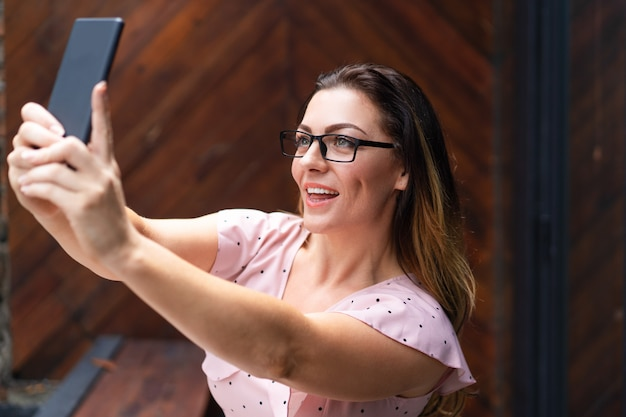 Donna graziosa sorridente che prende la foto del selfie sullo smartphone in caffè Foto Gratuite