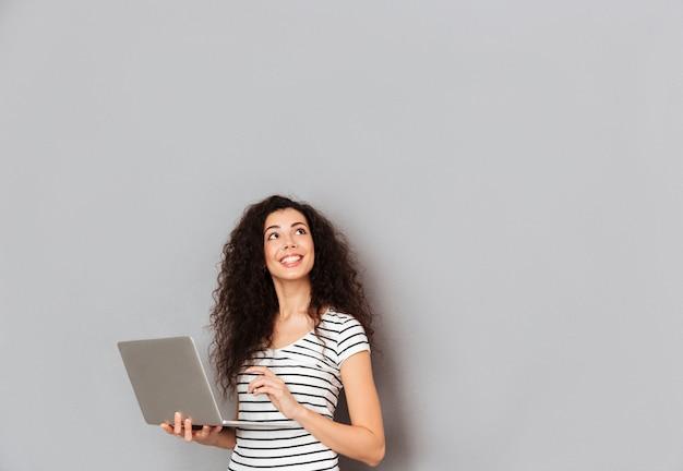 Donna graziosa sorridente in maglietta a strisce con il pensiero ascendente del fronte o sognare ad occhi aperti mentre lavorando tramite computer portatile che è isolato sopra la parete grigia Foto Gratuite