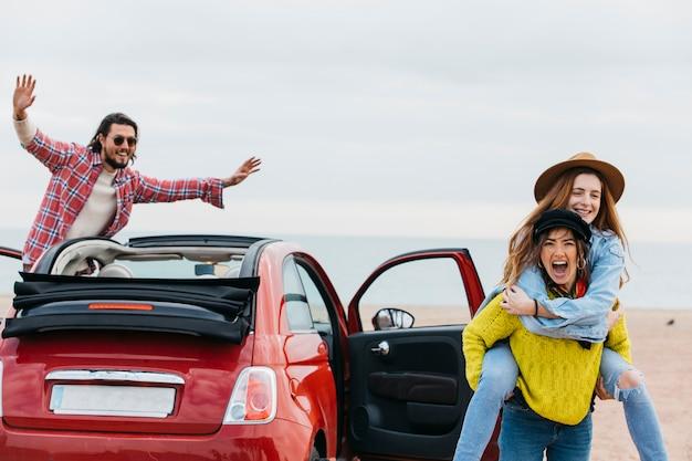 Donna gridante che tiene indietro signora felice vicino all'uomo che si appoggia fuori dall'automobile Foto Gratuite