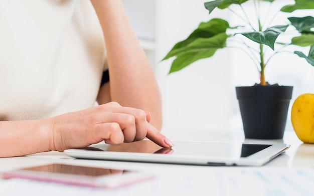 Donna in abiti leggeri utilizzando tablet al tavolo Foto Gratuite