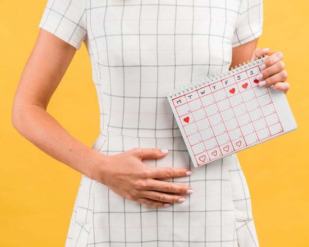 Donna in abito bianco con crampi allo stomaco dalle mestruazioni Foto Gratuite