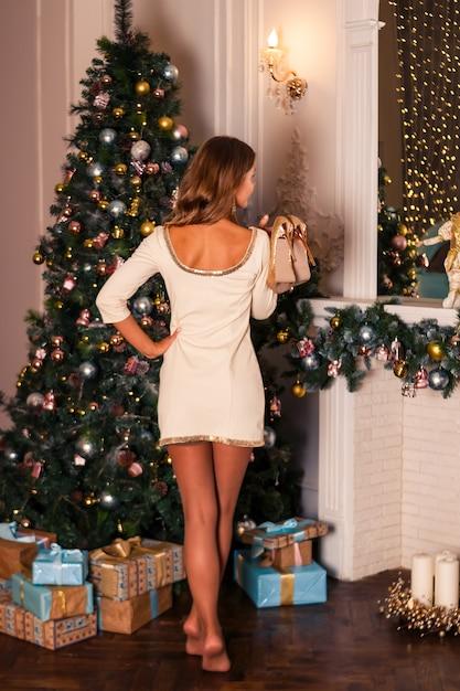 Donna in abito bianco girato in piedi vicino a un albero di natale Foto Premium