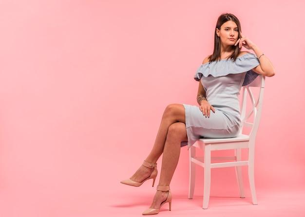 Donna in abito blu, seduto sulla sedia Foto Gratuite