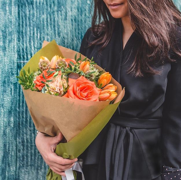 Donna in abito nero con bouquet misto in carta. Foto Gratuite