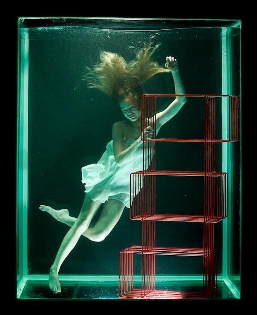 Donna in acqua con una libreria rossa Foto Gratuite