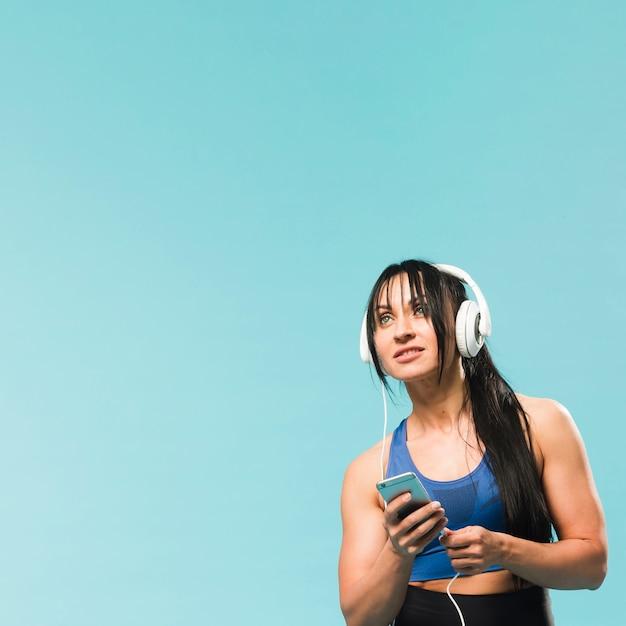 Donna in attrezzatura della palestra che ascolta la musica in cuffie Foto Gratuite