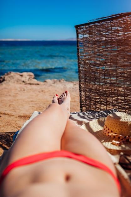 Donna in bikini che si rilassa sulla spiaggia che si trova sulle chaise longue con il mare e il mountain view. vacanze estive. Foto Premium