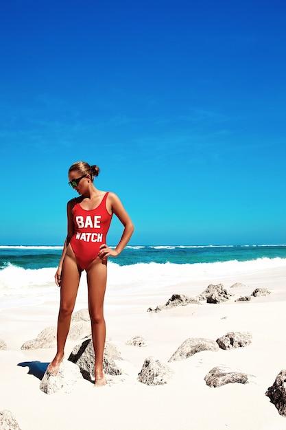 Donna in bikini rosso in posa sulla spiaggia estiva dietro cielo blu e mare Foto Gratuite