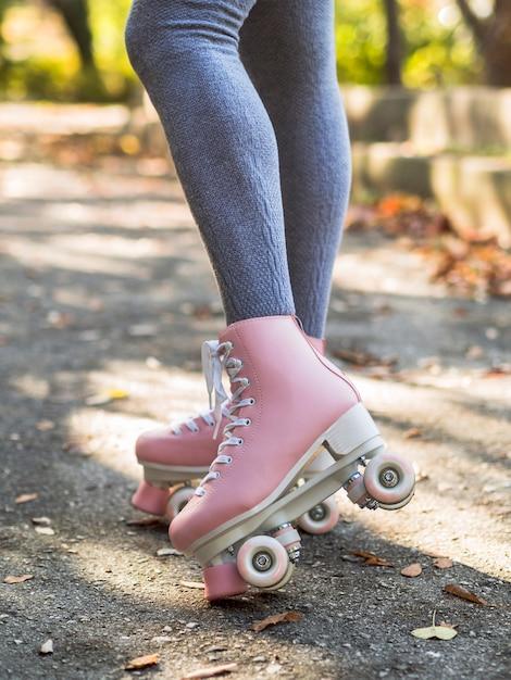 Donna in calzini in posa con pattini a rotelle Foto Gratuite