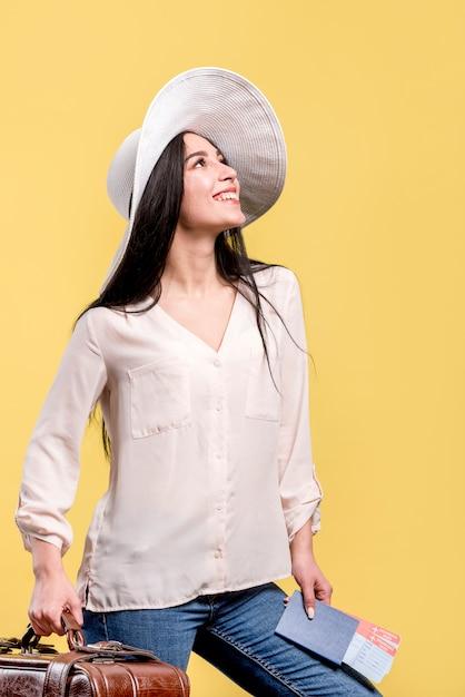 Donna in cappello che sorride e che tiene i biglietti e la valigia Foto Gratuite