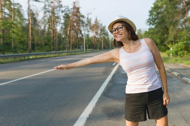 Donna in cappello che sta sulla strada che ferma automobile Foto Premium
