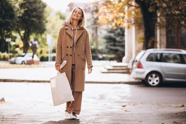 Donna in cappotto beige con la borsa della spesa in strada Foto Gratuite