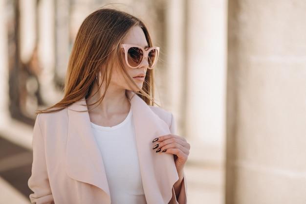 Donna in cappotto camminando per la strada Foto Gratuite