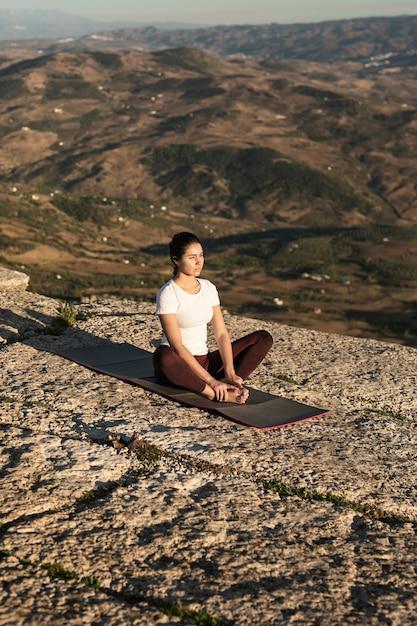 Donna in cima alla meditazione della montagna Foto Gratuite
