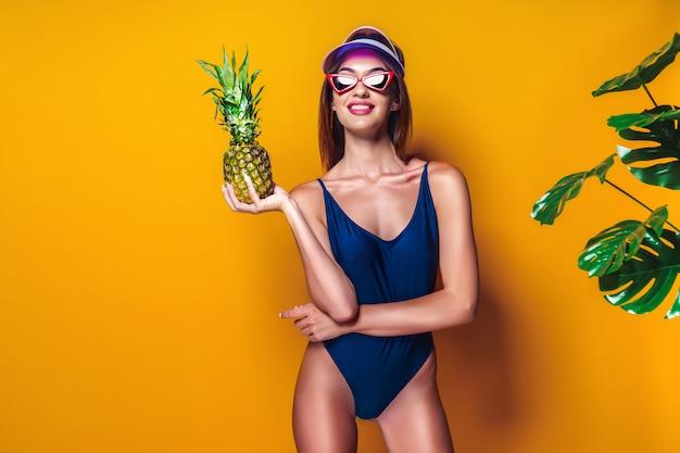 Donna in costume da bagno tenendo l'ananas Foto Premium
