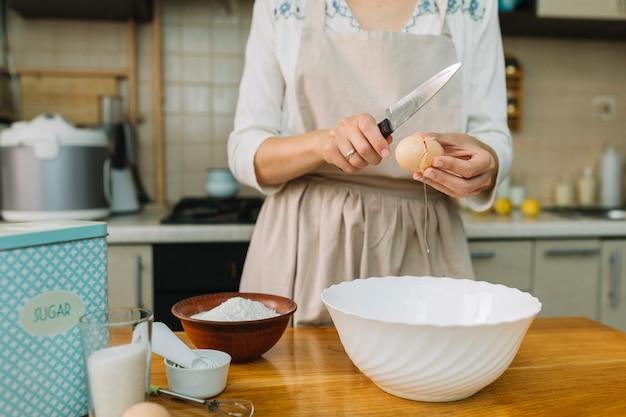 Donna in cucina rompendo l'uovo per la preparazione della ciotola Foto Gratuite