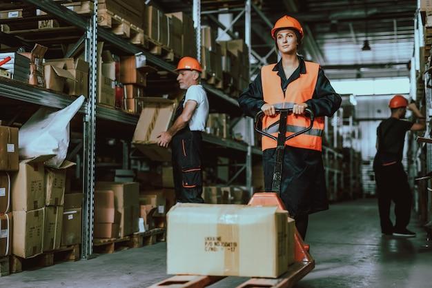 Donna in elmetto protettivo che utilizza il carrello del carrello elevatore nel magazzino Foto Premium