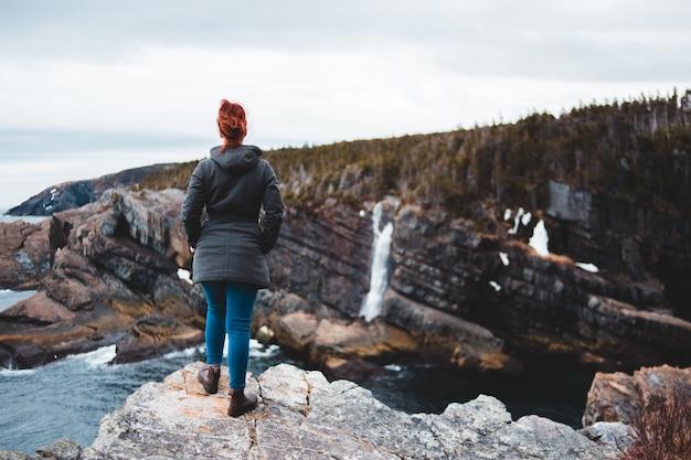 Donna in giacca nera in piedi sulla montagna rocciosa durante il giorno Foto Gratuite