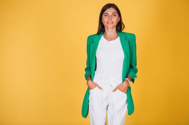 Donna in giacca verde in studio su sfondo giallo Foto Gratuite