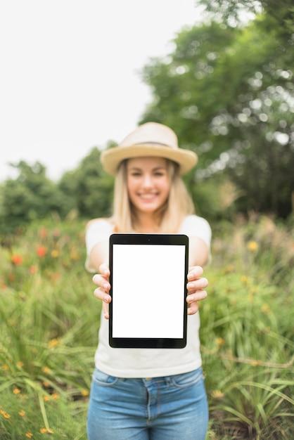 Donna in giardino che mostra tablet con schermo vuoto Foto Gratuite