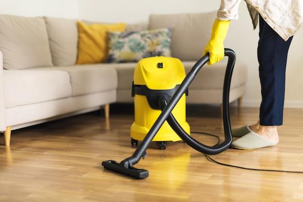 Donna in guanti protettivi pulizia del soggiorno con aspirapolvere giallo. concetto pulito Foto Premium