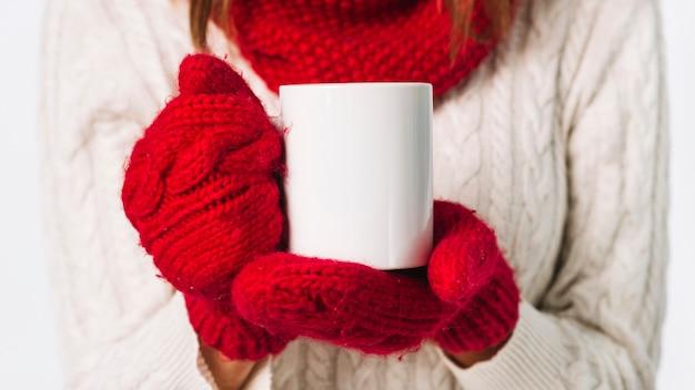 Donna in guanti tenendo la tazza Foto Gratuite