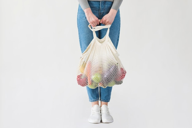 Donna in jeans che tengono borsa riutilizzabile con generi alimentari Foto Gratuite
