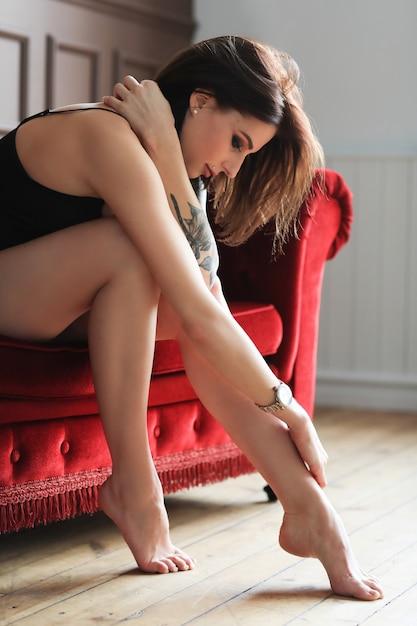 Donna in lingerie nera seduta sul divano di velluto rosso Foto Gratuite