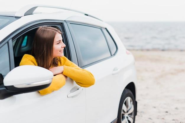 Donna in macchina guardando lontano Foto Gratuite