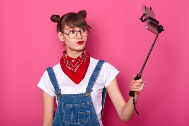 Donna in maglietta bianca casual, tuta, bandana rossa sul collo e occhiali rotondi. adorabile adolescente mantiene le labbra arrotondate Foto Gratuite