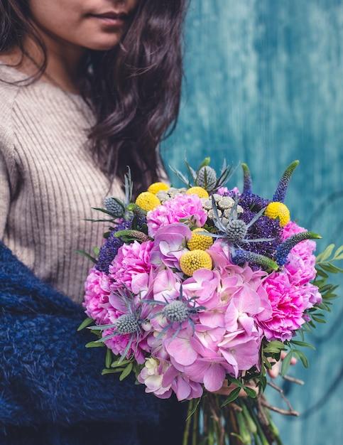 Donna in maglione beige con un bouquet di fiori misti. Foto Gratuite
