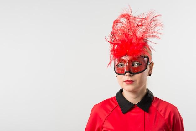 Donna in maschera con piume rosse Foto Gratuite