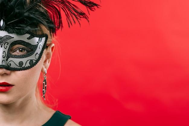Donna in maschera grigia con piume Foto Gratuite