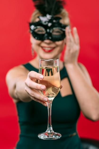 Donna in maschera nera che tiene il bicchiere di champagne Foto Gratuite